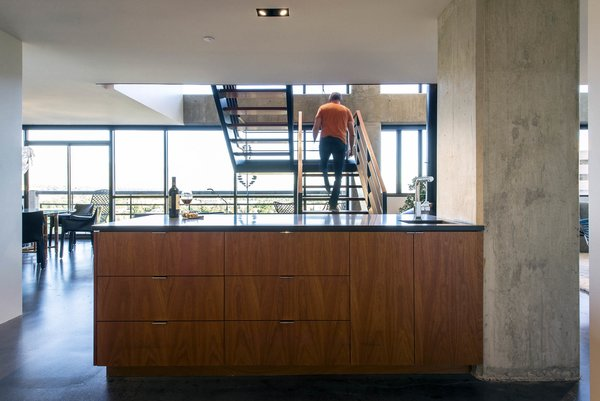 Modern home with kitchen, engineered quartz counter, wood cabinet, concrete floor, concrete backsplashe, and recessed lighting. kitchen island - looking toward staircase Photo 9 of Governors Plaza