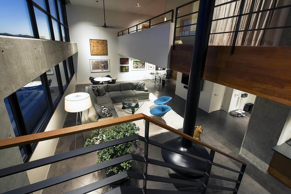 Modern home with living room, lamps, sectional, coffee tables, chair, floor lighting, recessed lighting, concrete floor, and hanging fireplace. two story volume - looking down at living room and office Photo 17 of Governors Plaza