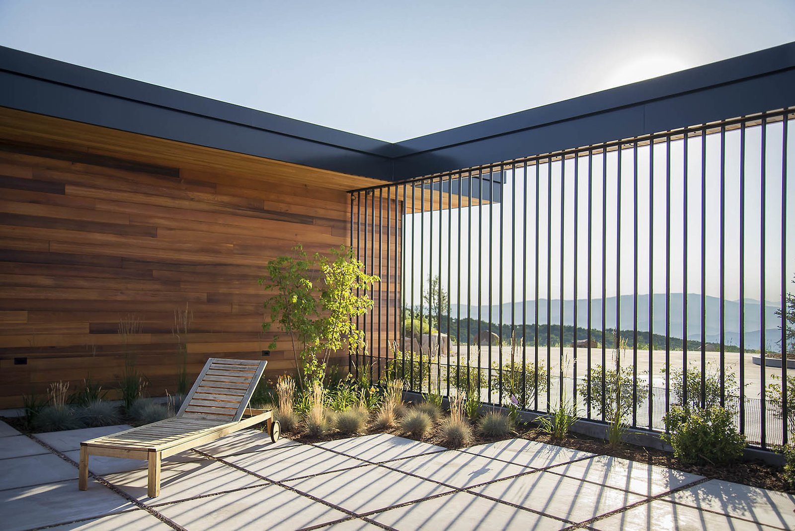 From the interior of the courtyard the blue Uintah Mountains can be seen sprawling along the horizon. Tagged: Outdoor, Front Yard, Trees, Shrubs, Grass, Hardscapes, Walkways, Large, Concrete, Vertical, Metal, and Pavers.  Best Outdoor Pavers Grass Photos from Red Hawk
