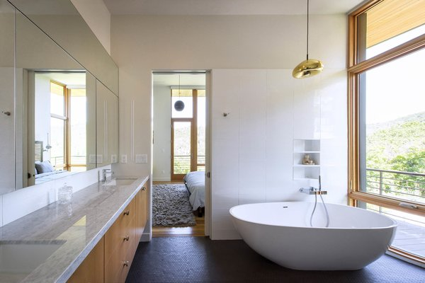 The master bathroom is flooded with light and views while maintaining privacy screened by the scrub oak preserved on lot.