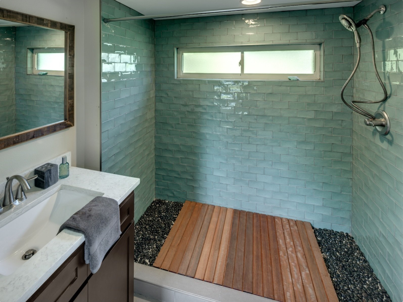 Bathroom with sea green tiles and Abaco flooring  Amplified Tiny House by Asha Mevlana