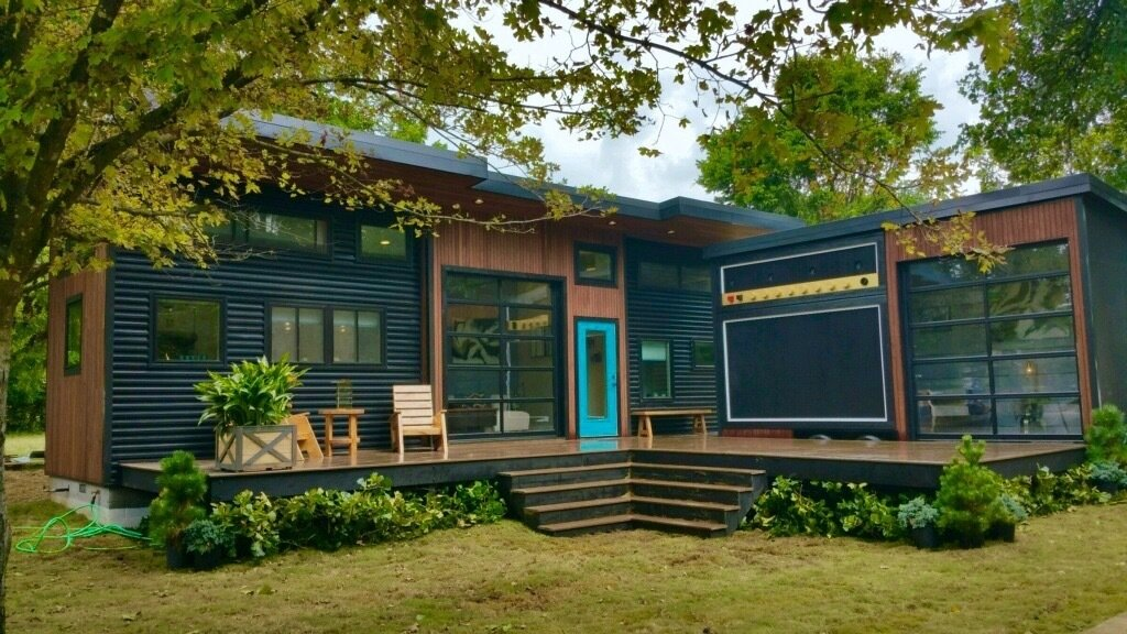 """Exterior of """"Amplified"""" Tiny House. Exterior furniture by Ecovet Furniture. Their furniture is custom built by veterans using reclaimed material from decommissioned trailers. Tagged: Exterior, House, Wood Siding Material, and Metal Siding Material. Amplified Tiny House by Asha Mevlana"""