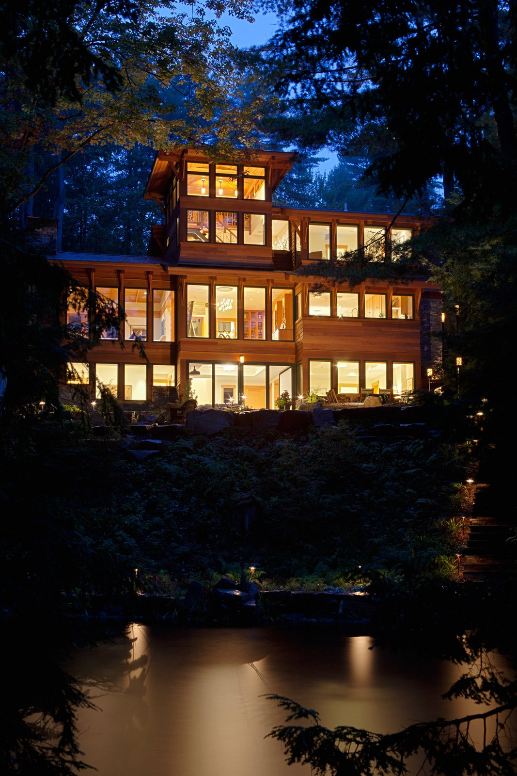 Nighttime view of house from Lake Luzerne  Fourth Lake Summer House by Phinney Design Group