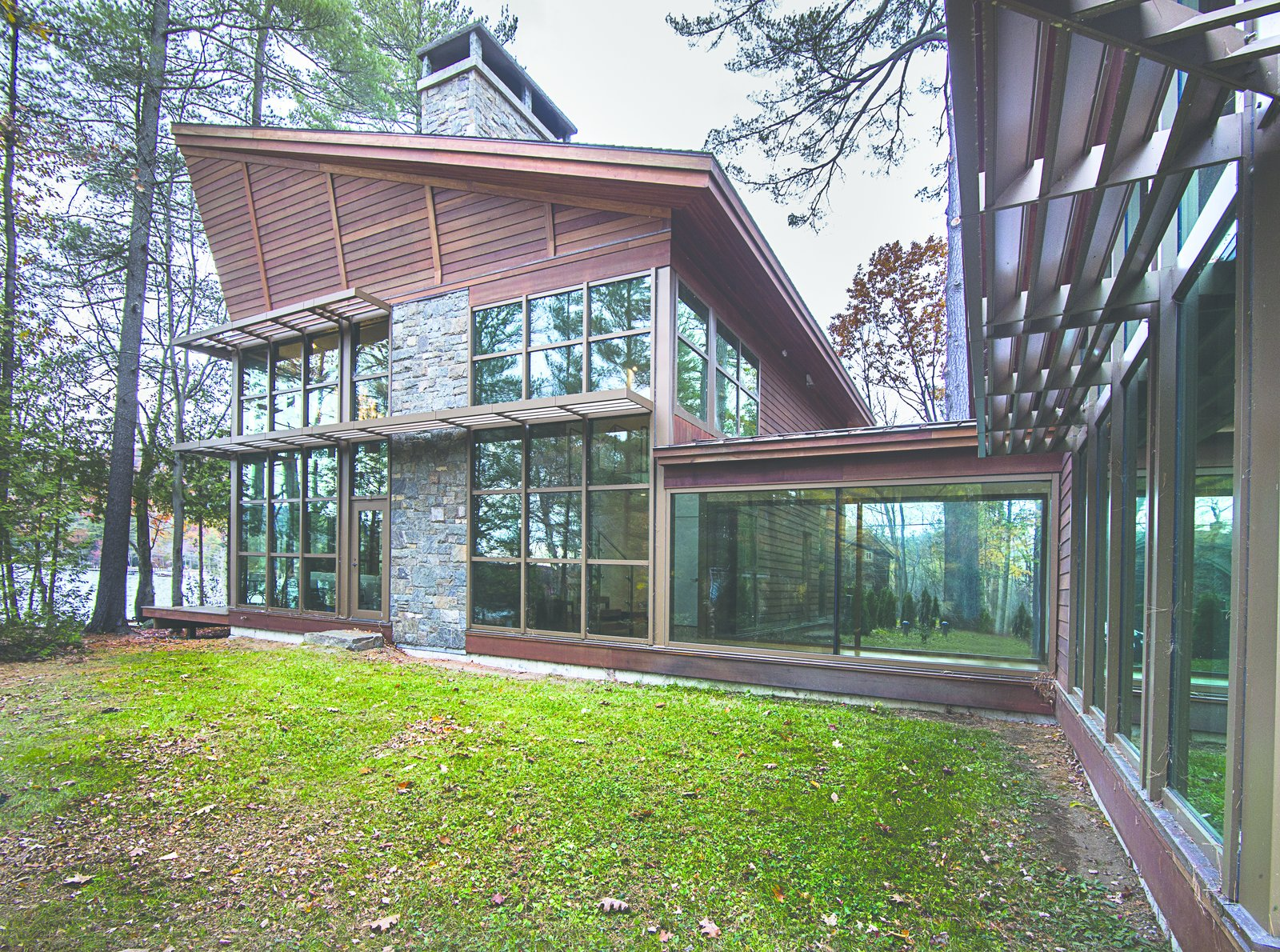 This lake house was designed in close collaboration with the client, an architect known for his architectural renderings and illustrations.  The exterior walls of the building were clad with glass to permit the site and the interior to act as one. Modern Adirondack Retreat by Phinney Design Group