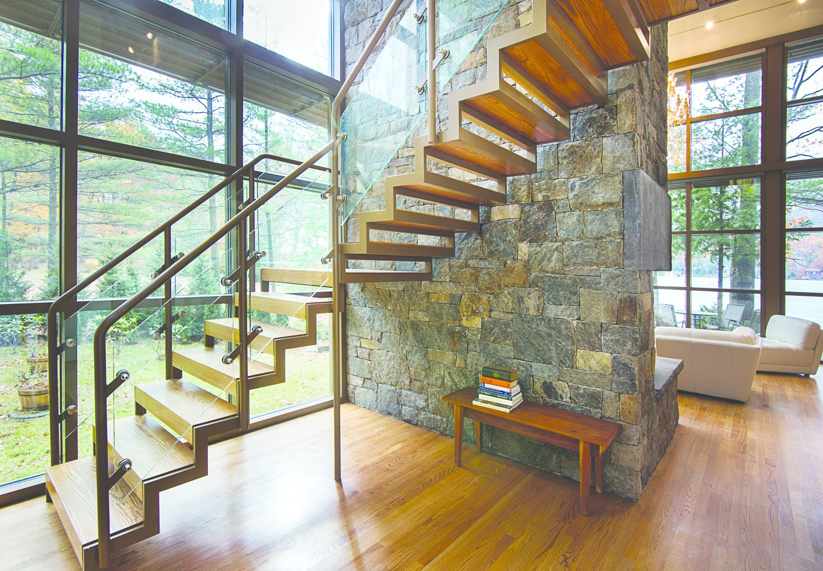 The sawtooth open staircase is anchored to granite chimney providing views of the stone through the stairway as well as, outside through the large glass wall behind the stair.  Modern Adirondack Retreat by Phinney Design Group