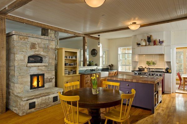 Locally harvested stone was used for the masonry heater.  This is also the architectural focus of the main living area.  Photo 4 of Barn Reinvented - LEED Platinum Home modern home
