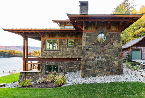 Exterior siding is a combination of locally milled douglas-fir timbers, eastern white bark-on cedar planks, poplar bark shakes and New Baltimore Stone which was quarried close to the project site.   Photo 6 of East Meets West in the Adirondacks modern home