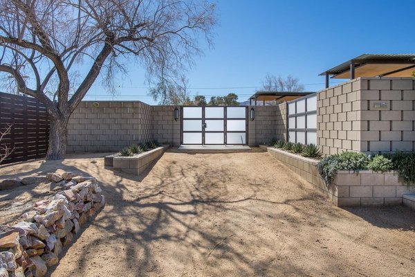 Modern home with plywood floor, carpet floor, front yard, desert, trees, shrubs, hardscapes, vertical fence, landscape lighting, post lighting, and outdoor. Front Entry showing decorative block walls with open perforations and protruding details.  Concrete block, metal with wood detail age well in the desert environment.  Photo  of Modern Jewel in the Desert