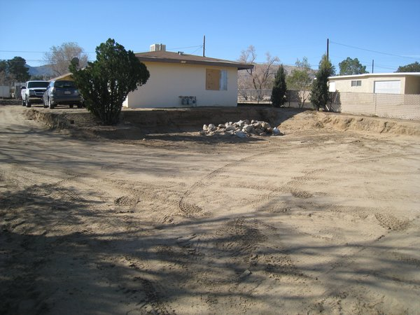 Modern home with outdoor, front yard, and desert. Photo showing front of building with dirt removed from front of building for future block wall.  This block wall will make the building seem taller than the one story it is now.  Photo 4 of Modern Jewel in the Desert