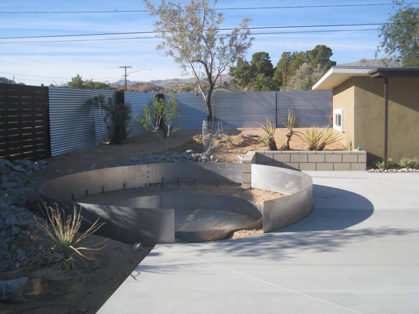 Modern home with outdoor, desert, back yard, and hardscapes. Metal formwork for the curved seating area.  The metal rusted by the rain.   Photo 13 of Modern Jewel in the Desert