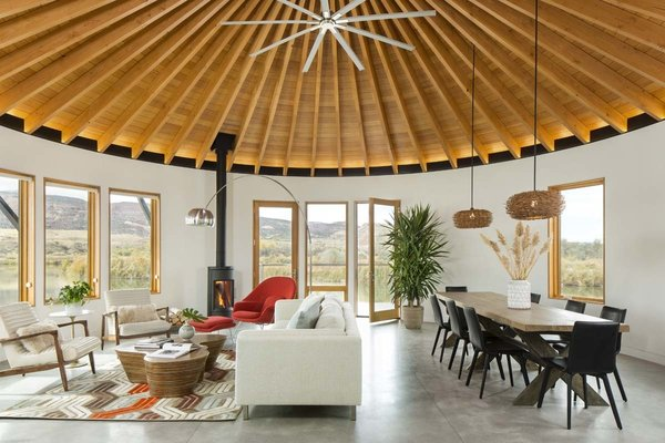 The largest of the three yurt structures houses the living and dining rooms and provides panoramic views. A geometric hide rug by Dedalo Rugs ties in pops of red from Eero Saarinen's Womb Chair, and pale blue from the Room and Board cushions on the sofa. The homeowners sourced the Oggetti Showtime coffee table from Wayfair. A pair of Kichler pendants define the dining area.