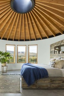 A Yurt-Inspired Vacation Home on the High Desert Plains of Colorado - Photo 4 of 8 - The ceiling of all three yurts is made with tongue-and-groove planks of Douglas fir that meet at a steel skylight at the center. A custom-made bed is complete with a linen duvet cover from Coyuchi and enticing sheepskin pillows.