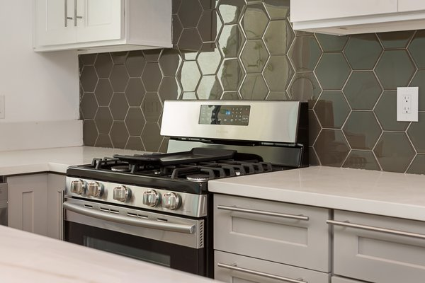 Modern home with kitchen, engineered quartz counter, white cabinet, wood cabinet, glass tile backsplashe, and range. Quartz countertops and glass hexagon tiles Photo 9 of Briarwood Place