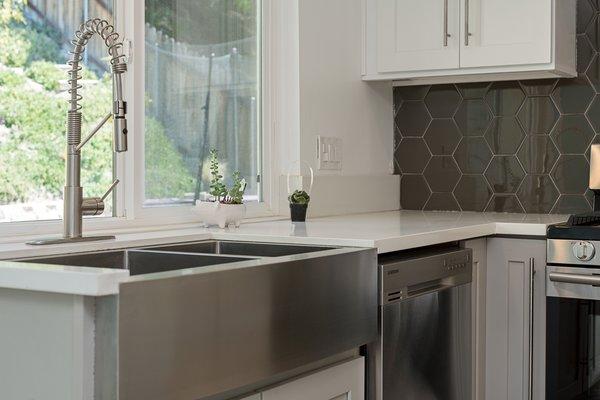 "Modern home with kitchen, engineered quartz counter, wood cabinet, white cabinet, dishwasher, range, and glass tile backsplashe. Kraus 36"" Apron sink Photo 12 of Briarwood Place"