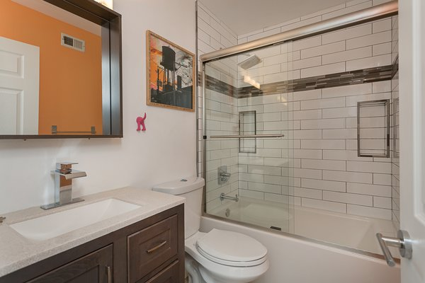 Modern home with bath room, drop in sink, porcelain tile floor, soaking tub, granite counter, enclosed shower, recessed lighting, wall lighting, glass tile wall, subway tile wall, and one piece toilet. Hallway bathroom Photo 19 of Briarwood Place