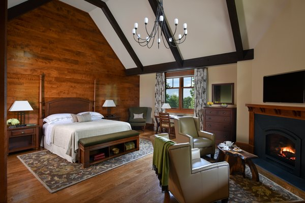 The 7,000-square-foot two-story Grove Lodge incorporates the use of native stone and natural finishes to help it blend into the scenic landscape of the Mohonk Mountain House property.  Interior spaces include hardwood floors and the use of exposed wood throughout. The guest rooms have their own separate drive-up entrances and feature either a stone patio (lower level) or balcony area. All areas are appointed with our rustic rocking chairs for outdoor seating.  Eco-friendly features include sustainable building materials, LED lighting, and a geo- thermal heating and cooling system. 250-tons of Shawangunk conglomerate excavated from the site have been recycled into the retaining walls and the stone fireplace. Photo 2 of Grove Lodge at Mohonk Mountain House modern home
