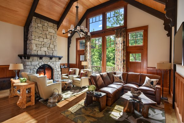 The 7,000-square-foot two-story Grove Lodge incorporates the use of native stone and natural finishes to help it blend into the scenic landscape of the Mohonk Mountain House property.  Interior spaces include hardwood floors and the use of exposed wood throughout. The guest rooms have their own separate drive-up entrances and feature either a stone patio (lower level) or balcony area. All areas are appointed with our rustic rocking chairs for outdoor seating.  Eco-friendly features include sustainable building materials, LED lighting, and a geo- thermal heating and cooling system. 250-tons of Shawangunk conglomerate excavated from the site have been recycled into the retaining walls and the stone fireplace. Photo  of Grove Lodge at Mohonk Mountain House modern home