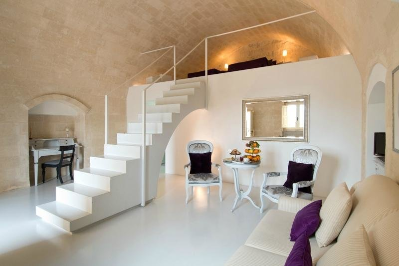 Set in the ancient cave dwellings in the ancient Italian city of Sassi de Matera, Sant'Angelo Luxury Resort combines the curving outlines and texture of natural stone with soft modern touches. Tagged: Living Room, Sofa, and Chair.  Photo 4 of 11 in Ever Wanted to Stay in a Cave That's Actually Pretty Modern Inside?