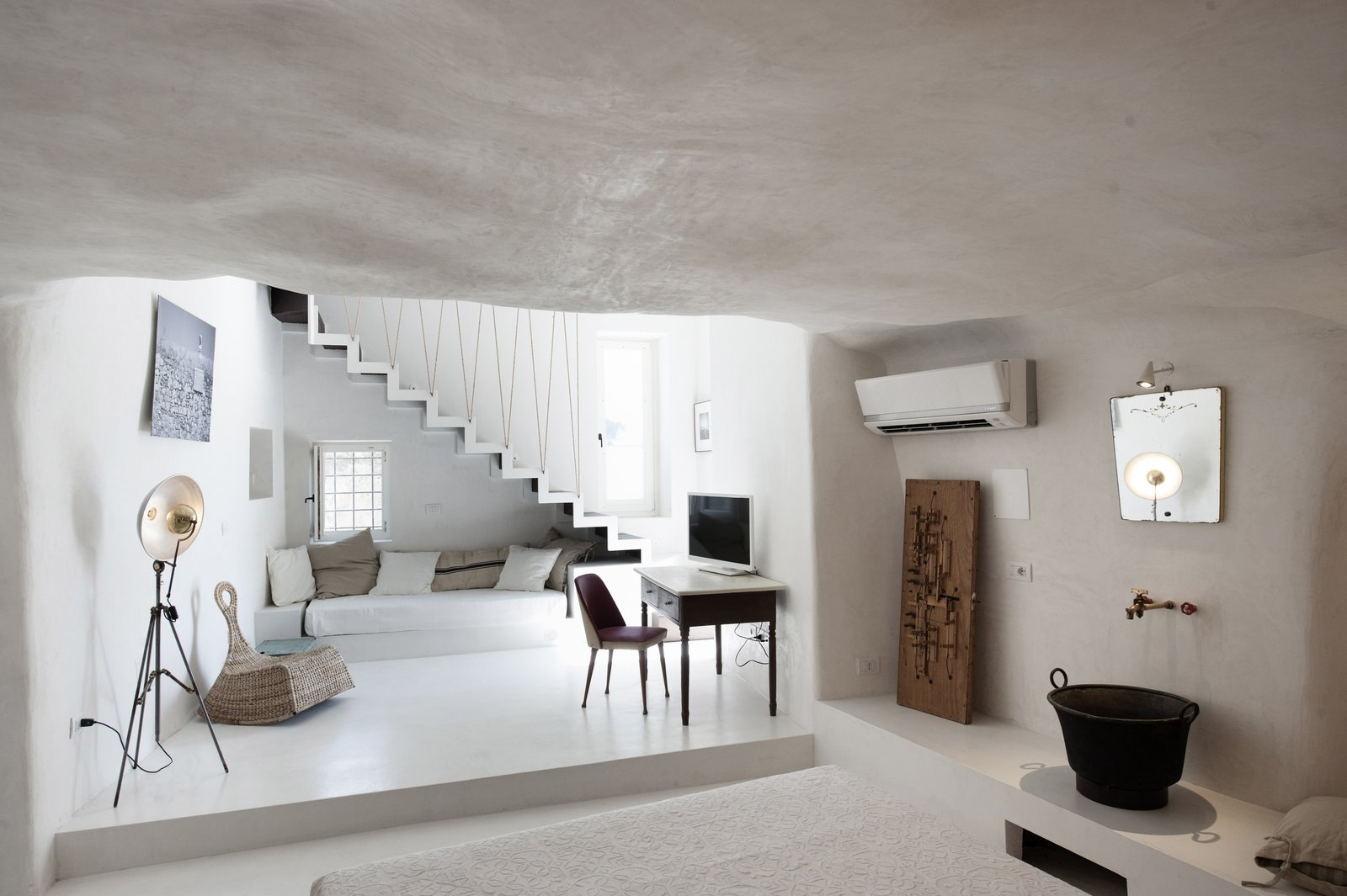 After relocating from Milan to the small Baroque town of Modica in Sicily, architect couple Marco Giunta and Viviana Haddad  purchased and restored an old house they found with locally sourced stones, tiles and plaster. They now operate it as Casa Talia – a boutique hotel where guests can experience life at a more leisurely pace. Tagged: Living Room, Lamps, Chair, Floor Lighting, Bench, and Concrete Floor.  Photo 6 of 11 in Ever Wanted to Stay in a Cave That's Actually Pretty Modern Inside?