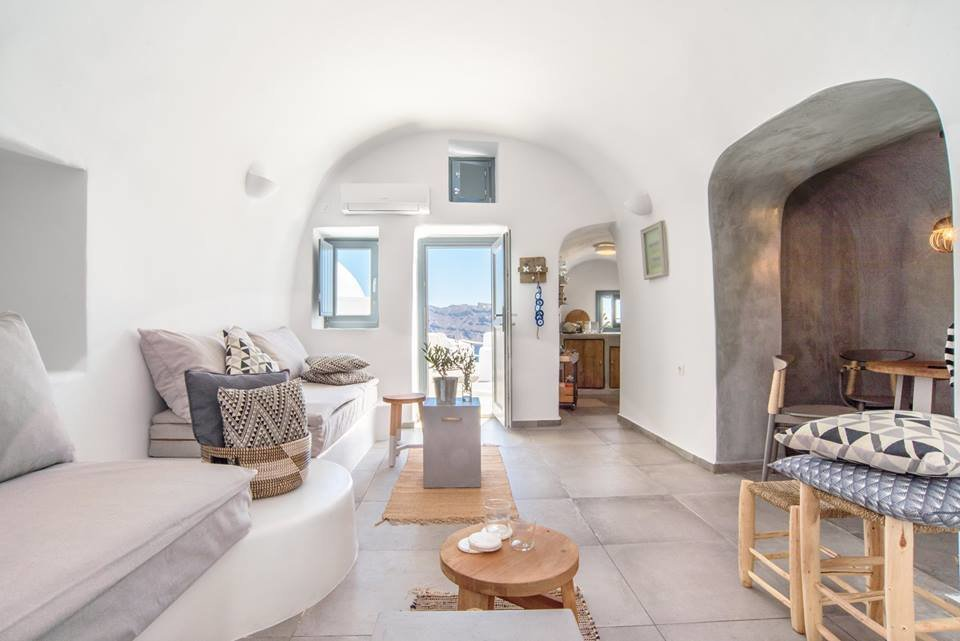 Carved into the majestic Caldera cliffs of Santorini's most famous village – Oia, this yposkafo was renovated in 2016 and comes with an indoor and outdoor and an inviting interior decorated in soft greys and blues. Tagged: Living Room, Bench, Wall Lighting, and Limestone Floor. Ever Wanted to Stay in a Cave That's Actually Pretty Modern Inside? - Photo 8 of 11