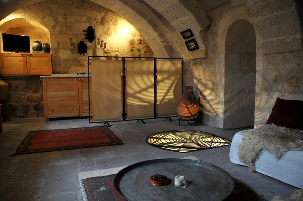 The three suites of Asmali Cave House in Cappadocia come with living rooms and kitchens, spacious bedrooms and unusual bathrooms. Tagged: Bath Room, Limestone Floor, and Wall Lighting.  Photo 10 of 11 in Ever Wanted to Stay in a Cave That's Actually Pretty Modern Inside?
