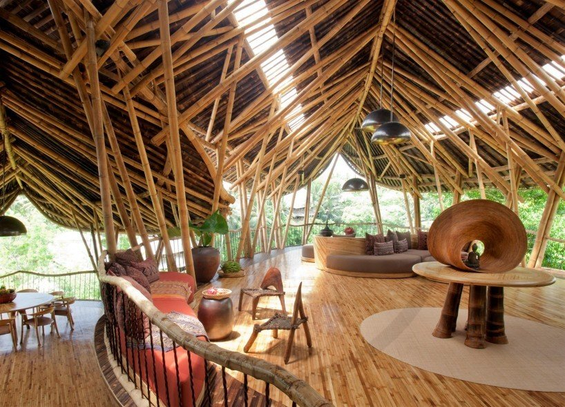 Part of the Green Village Residential Community in Ubud, Bali, this unique, sculptural house designed by Elora Hardy of Ibuku is built almost entirely from locally sourced bamboo. Tagged: Living Room, Bench, Coffee Tables, Chair, Pendant Lighting, and Light Hardwood Floor.  Photo 9 of 11 in Escape to the Jungle in One of These Modern Forested Retreats