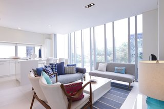 Experience a Modern, Eclectic Side of Singapore at One of These 10 City Stays - Photo 13 of 13 - Decked out in plenty of white and cool grays and blues, this two-bedroom apartment sits in a luxury condominium in the heart of Singapore's city center. Its floor-to-ceiling windows in the living room offer immersive views of the city.