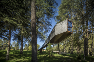 Get Back to Basics by Staying at One of These Modern Cabins - Photo 9 of 10 - Part cabin, part tree house, and covered in slate and wood, Tree Snake House in Portugal's Pedras Salgadas Park was designed by architect Luís Rebelo de Andrade and has windows that offer prime views of the forest and the starlit sky.