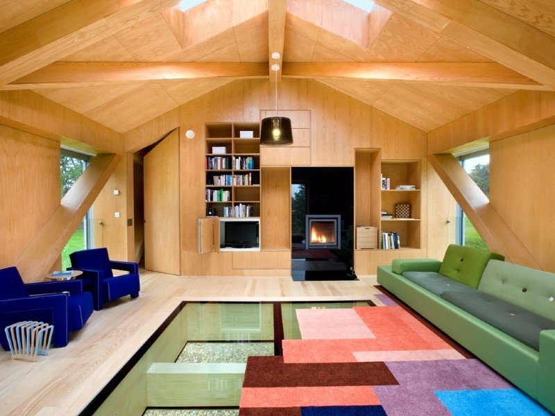 Tagged: Living Room, Pendant Lighting, Wood Burning Fireplace, Sofa, and Light Hardwood Floor.  Photo 5 of 11 in Take a Modern British Holiday in a Gleaming Cantilevered Barn
