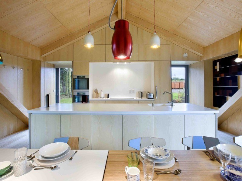 Tagged: Kitchen, Pendant Lighting, Engineered Quartz Counter, Microwave, Wall Oven, and Undermount Sink.  Photo 6 of 11 in Take a Modern British Holiday in a Gleaming Cantilevered Barn