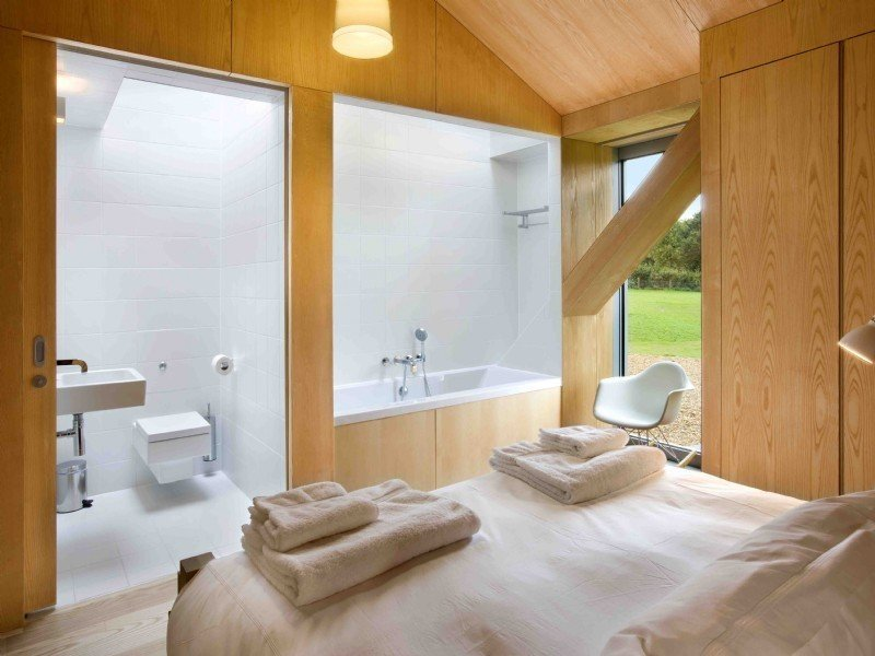 Tagged: Bath Room, Alcove Tub, Ceramic Tile Floor, One Piece Toilet, Ceramic Tile Wall, Wall Mount Sink, and Soaking Tub.  Photo 8 of 11 in Take a Modern British Holiday in a Gleaming Cantilevered Barn