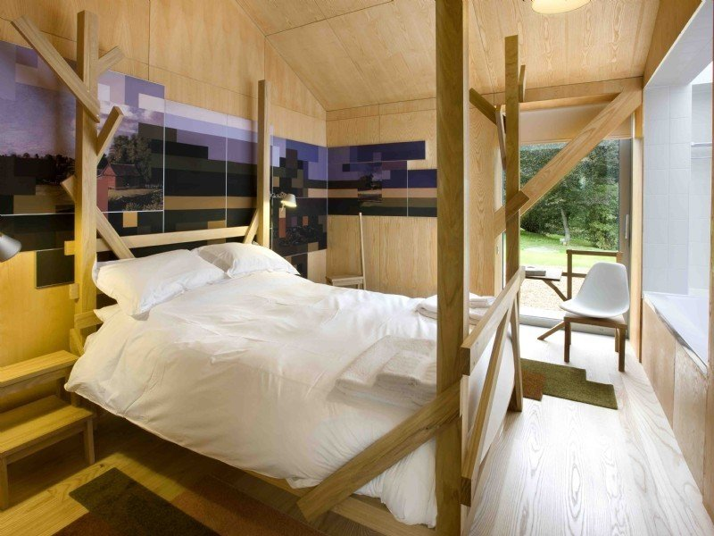 Tagged: Bedroom, Bed, Chair, and Light Hardwood Floor. Take a Modern British Holiday in a Gleaming Cantilevered Barn - Photo 9 of 11