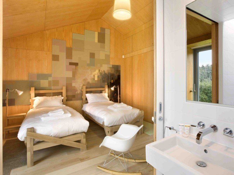 Tagged: Bedroom, Chair, Bed, Rockers, Lamps, Wall Lighting, Ceiling Lighting, and Light Hardwood Floor.  Photo 10 of 11 in Take a Modern British Holiday in a Gleaming Cantilevered Barn