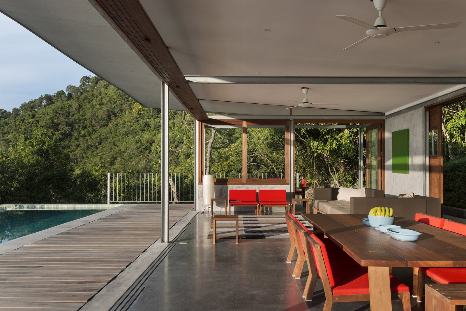 Tagged: Infinity Pools, Tubs, Shower, Sofa, Wood Patio, Porch, Deck, Concrete Patio, Porch, Deck, Bookcase, Chair, and Outdoor.  Photo 4 of 11 in Take a Trip to This Photographer-Designed Concrete Home in Thailand