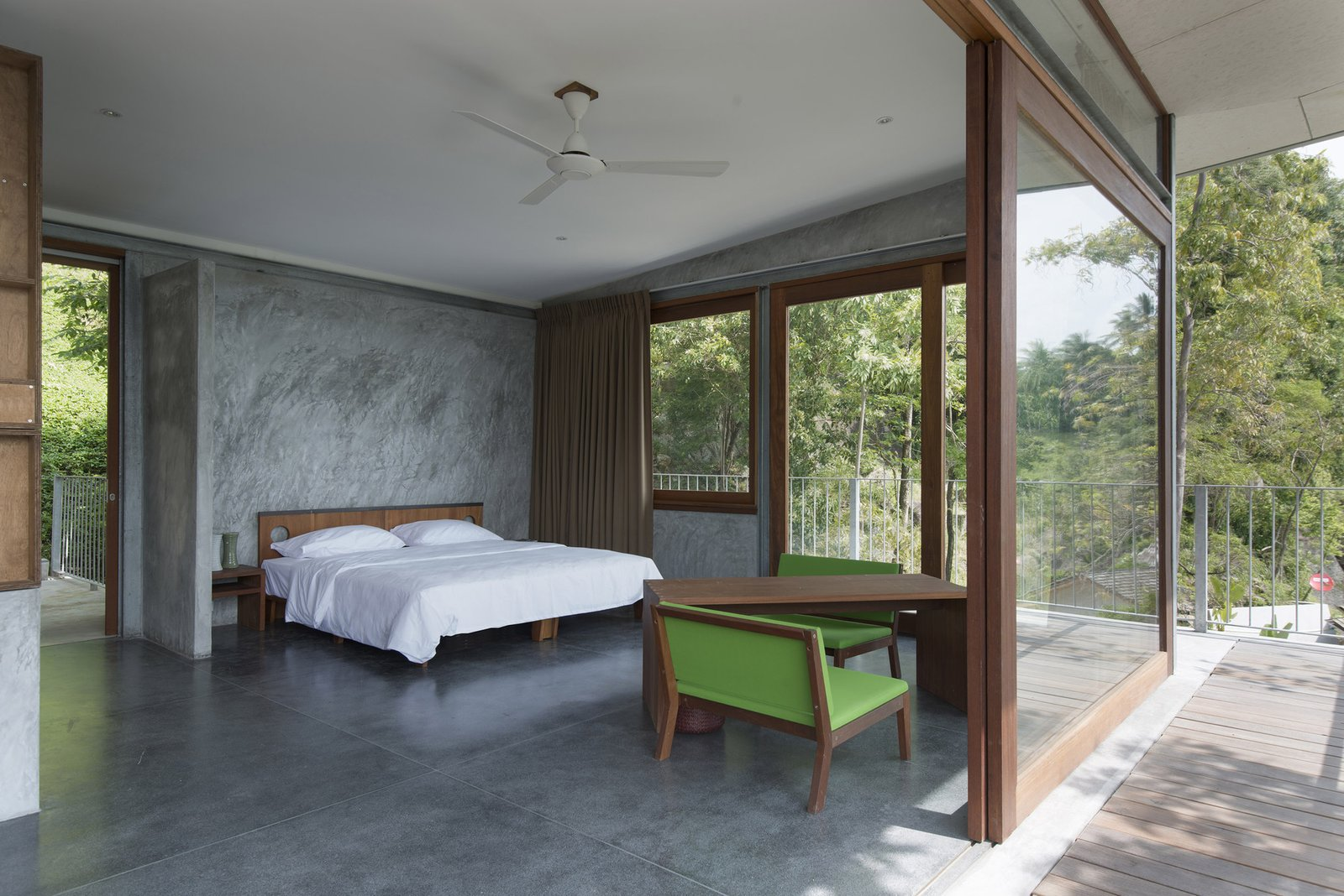 Tagged: Trees, Side Yard, Sofa, Chair, Metal Fences, Wall, Ceiling Lighting, Cooktops, Bedroom, and Concrete Floor.  Photo 8 of 11 in Take a Trip to This Photographer-Designed Concrete Home in Thailand