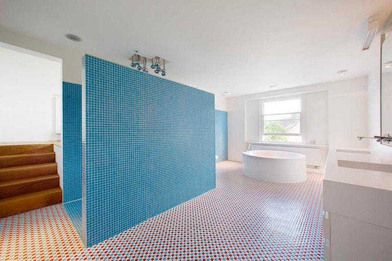 Tagged: Storage, Bed, Freestanding Tub, Table, Shelves, Light Hardwood Floor, Bath Room, Soaking Tub, and Ceiling Lighting. Bright Bauhaus Colors Fill This Brick Edwardian House in London - Photo 11 of 13
