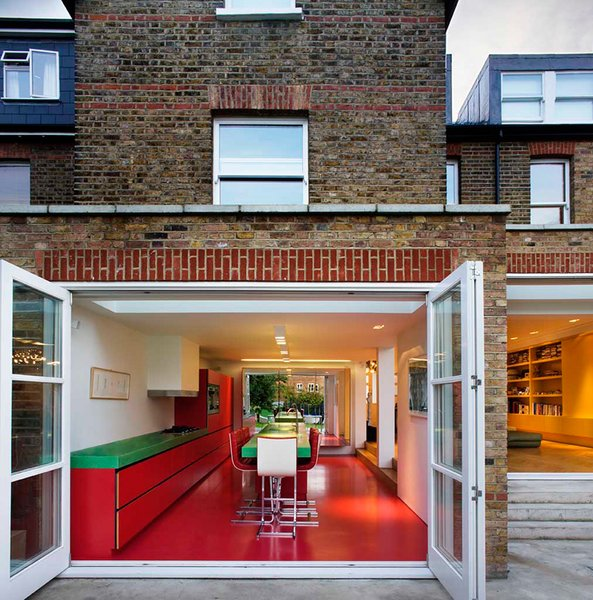 London architecture studio AMA remodeled this home in an old Edwardian building with bold Bauhaus colors, and transformed the kitchen into an audacious red and green space with glossy vermillion floors.
