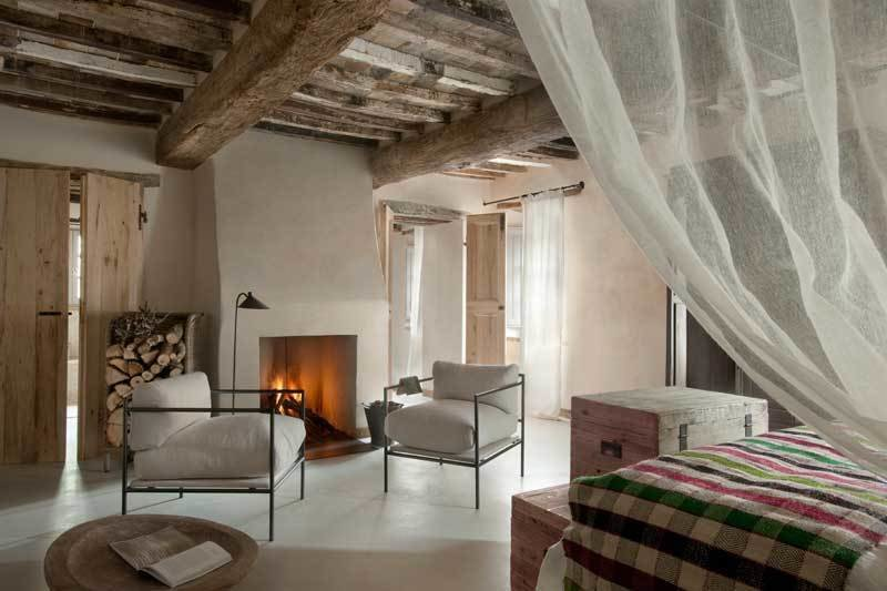 Tagged: Bedroom, Bed, Concrete Floor, Chair, and Floor Lighting.  Photo 3 of 10 in Rustic Meets Modern In This Tuscan Village Boutique Hotel