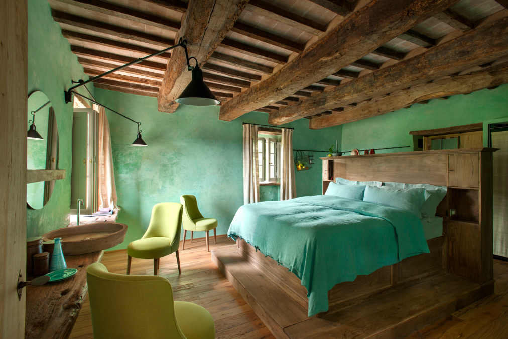 Tagged: Bedroom, Wall Lighting, Chair, Bed, and Medium Hardwood Floor.  Photo 10 of 10 in Rustic Meets Modern In This Tuscan Village Boutique Hotel