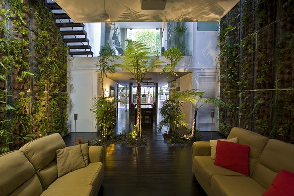Modern home with sofa, front yard, metal tread, wood patio, porch, deck, trees, dark hardwood floor, and living room. Photo 5 of Tree House at Jalan Elok