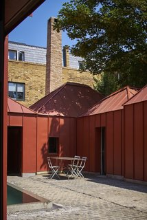 10 Homes With Large, Well-Ventilated Courtyards - Photo 8 of 9 - Six earth-colored, metal-clad pavilions were combined to create Tin House, an innovative and voluminous house that boasts a secluded rectangular pool in a bright interior courtyard.