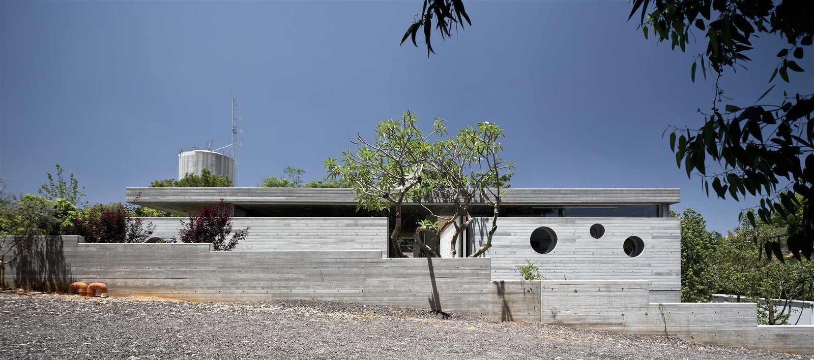 At the family home Israeli architect Pitsou Kedem, modern and light-filled interiors enliven a brutalist, raw concrete structure in the city of Ramat HaSharon near Tel Aviv.
