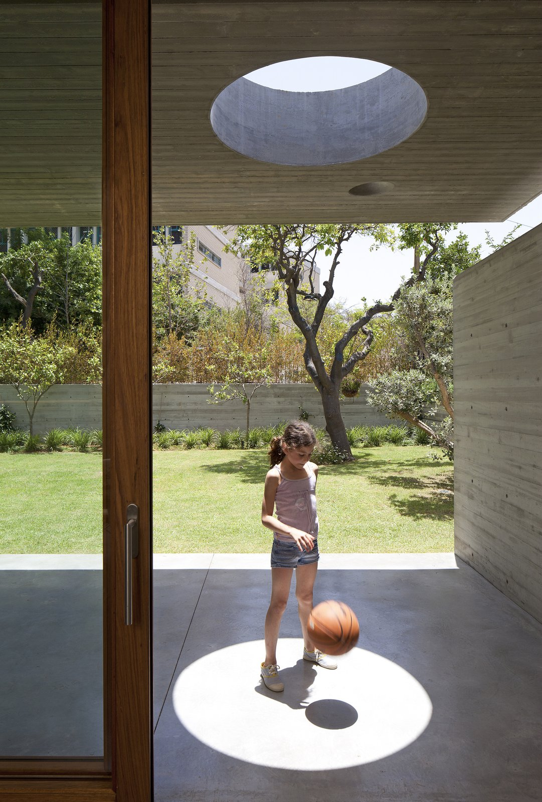 Tagged: Grass, Trees, Back Yard, Concrete Patio, Porch, Deck, Windows, and Skylight Window Type.  Photo 5 of 13 in An Architect's Bright and Airy Family Home Thrives Within a Brutalist Concrete Structure