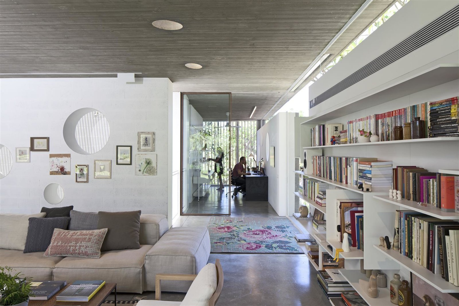 Tagged: Living Room, Ceiling Lighting, Sofa, Bookcase, and Concrete Floor.  Photo 7 of 13 in An Architect's Bright and Airy Family Home Thrives Within a Brutalist Concrete Structure