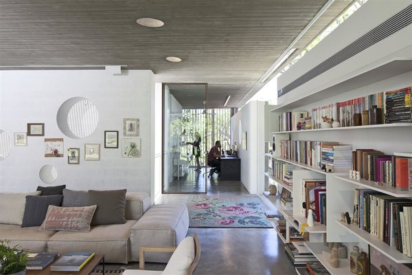 Modern home with living room, ceiling lighting, sofa, bookcase, and concrete floor. Photo 7 of House of an Architect
