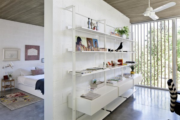 Modern home with bedroom, bed, shelves, table lighting, and concrete floor. Photo 10 of House of an Architect