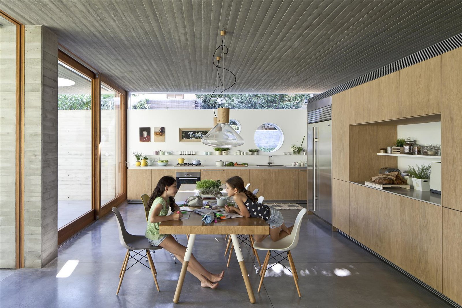 Tagged: Kitchen, Wood Cabinet, Concrete Floor, Ceiling Lighting, Refrigerator, Dishwasher, Range, Cooktops, and Drop In Sink.  Photo 12 of 13 in An Architect's Bright and Airy Family Home Thrives Within a Brutalist Concrete Structure