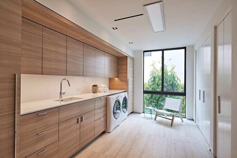 Designed by Miami firm, One D+B Architecture, laundry room has plenty of natural light, tall wardrobes and clean and simple warm wood everywhere. Tagged: Bath Room, Undermount Sink, Recessed Lighting, Ceiling Lighting, and Light Hardwood Floor.  Photo 3 of 8 in 7 Modern Laundry Rooms