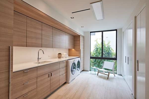 Designed by Miami firm, One D+B Architecture, laundry room has plenty of natural light, tall wardrobes and clean and simple warm wood everywhere.