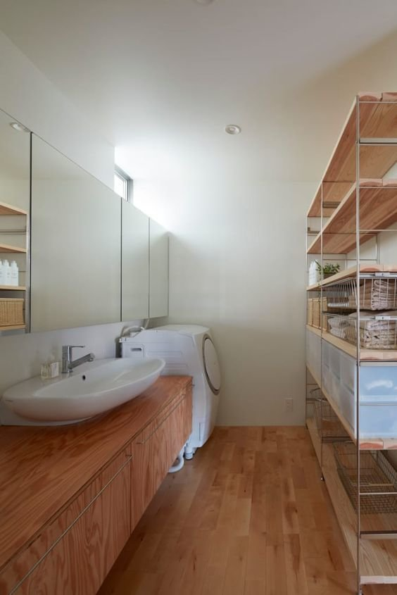 A slim shelf of raw wood and metal and mirrors lining one side of the wall, creates the illusion of expansiveness in this laundry room in a Japan home designed by Koizumisekkei.  Photo 5 of 8 in 7 Modern Laundry Rooms
